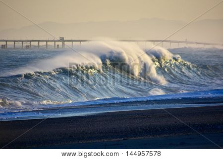 Big wave with foam breaking on the beach.