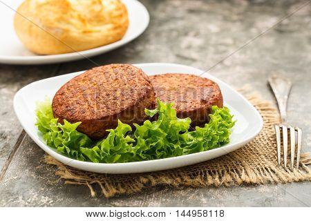 two vegetarian burgers and potato bun and salad.
