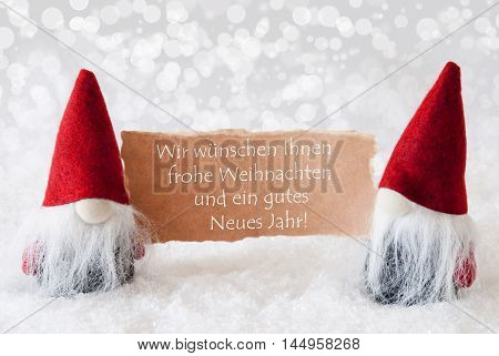Christmas Greeting Card With Two Red Gnomes. Sparkling Bokeh Background With Snow. German Text Frohe Weihnachten Und Ein Gutes Neues Jahr Means Merry Christmas And A Happy New Year