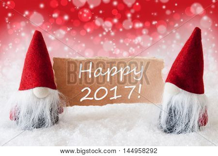 Christmas Greeting Card With Two Red Gnomes. Sparkling Bokeh And Christmassy Background With Snow. English Text Happy 2017