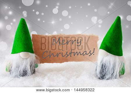 Christmas Greeting Card With Two Green Gnomes. Sparkling Bokeh And Noble Silver Background With Snow. English Text Merry Christmas