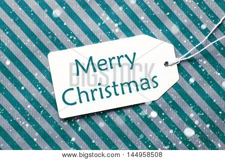 One Label On A Turquoise Striped Wrapping Paper. Textured Background With Snowflakes. Tag With Ribbon. English Text Merry Christmas