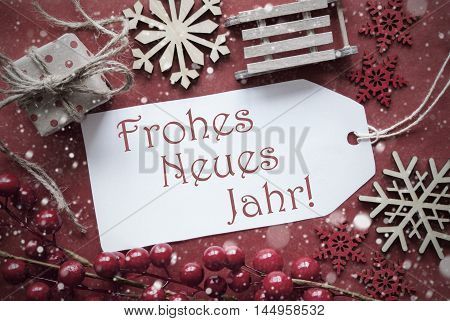 Nostalgic Christmas Decoration Like Gift Or Present, Sleigh. Card For Seasons Greetings With Red Paper Background. German Text Frohes Neues Jahr Means Happy New Year