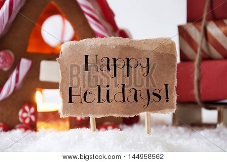 Gingerbread House In Snowy Scenery As Christmas Decoration. Sleigh With Christmas Gifts Or Presents. Label With English Text Happy Holidays
