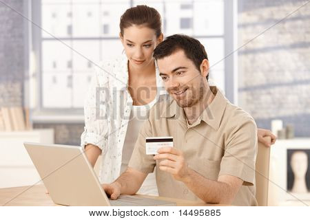 Happy couple using laptop, shopping online at home, using credit card.?