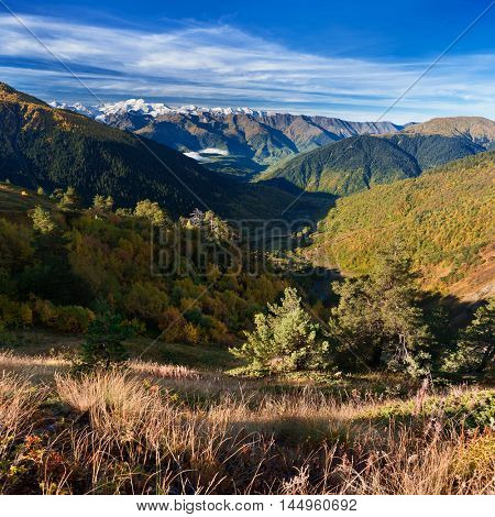 Autumn landscape in the mountains. The forests on the hillsides. View of the valley from the village. Sunny day. Zemo Svaneti, Georgia.