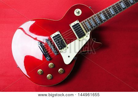 Deep red metallic solid body electric guitar on deep red background.