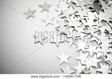 Silver stars spilling out on white surface. intentionally shot in surreal tone with vignetting. Extremely shallow depth of field.