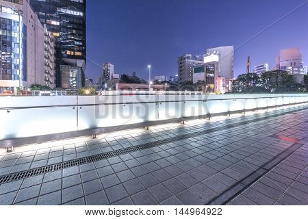 cityscape and skyline of tokyo at night from footpath