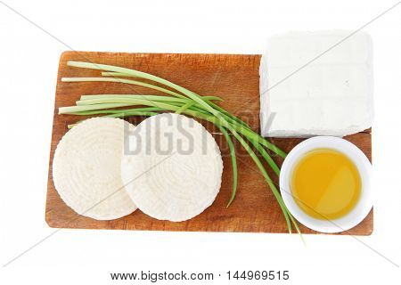 dairy food : feta white cheese cubes with olive oil on small saucer on cut wooden plate isolated over white background