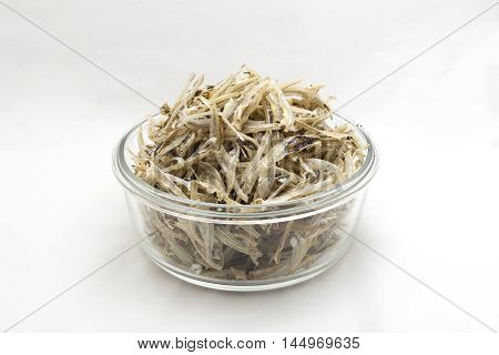 Small dried fish in a glass cup on a white background