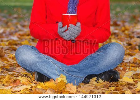 Hand Of Woman With Hot Drink Tea Or Coffee In Autumn Park