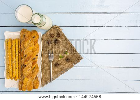 Breadsticks and milk on sky blue table background.Snack with meal or food of relax and holiday.Top view.1