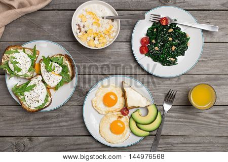 Breakfast table with healthy food. Fried eggs salad of spinach leaves avocado oatmeal cheese sandwich poached eggs and orange juice top view