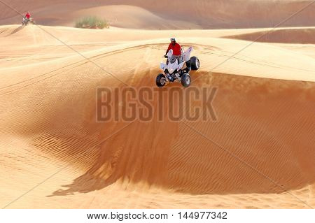 Extreme sport. ATV drives off the sand dunes