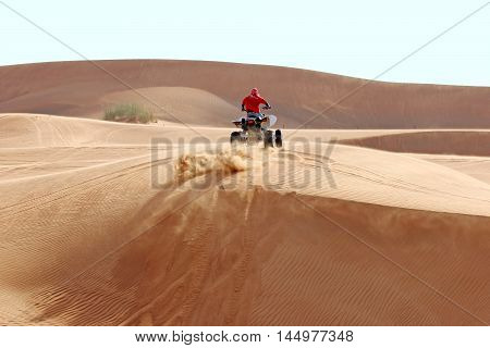 Sand flies out from under the wheels of the ATV