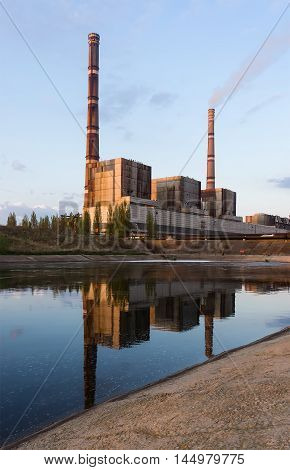 Industrial power plant with two smokestack and reflection