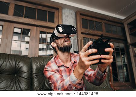 Man in vr glasses controlling something invisible. Young male playing video games with virtual reality headset and joystick or driving with remote control.