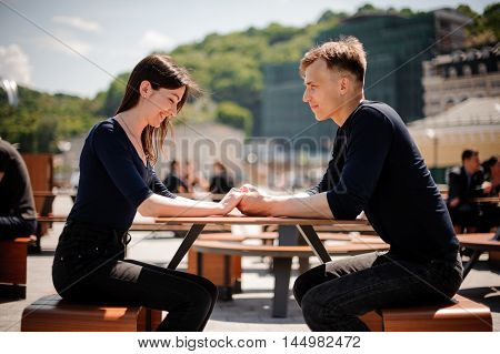 Young, happy couple smiling and holding hands across the table at a restaurant. Horizontally framed photo.