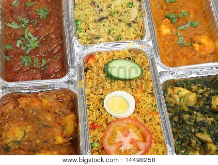 Indian curries with rice in takeaway food containers.