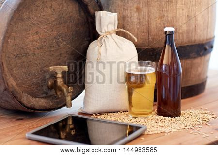 brewery, drinks and alcohol concept - close up of old beer barrel, glass bottle, tablet pc computer and bag with malt on wooden table