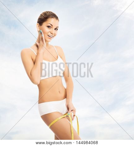 Young, sporty, fit and beautiful girl with the measuring tape over cloudy sky background.