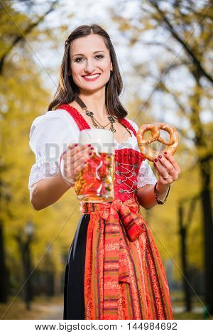 Woman in traditional Dirndl, carrying a beer mug and a Pretzel, standing
