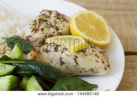 Fresh green salad white chicken meat baked with thyme and served with lemon and white rice