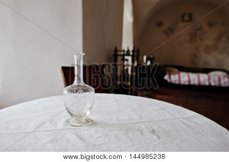 Old Vintage Decanter At A Round Table With A Tablecloth Background Old Room