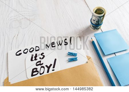 Card it's a boy with blue stickers, pencil and money, close-up. Note with congratulation about newborn child gender, white wooden background, free space