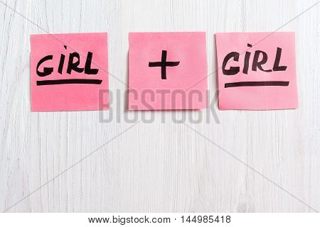 Pink stickers with girl plus girl text, copy space. Flat lay of three sheets of paper on white wooden background, free space. It's a girl twins concept