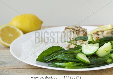 Green spinach salad with cucumber slices white rice and baked chicken meat served with lemon on a white plate. Healthy eating concept