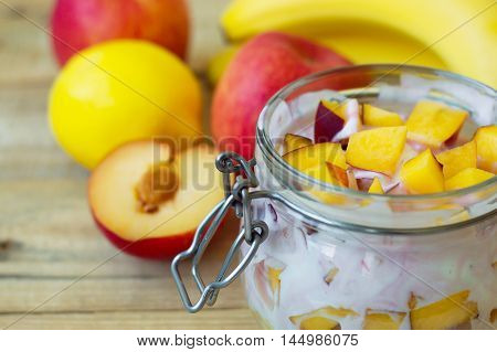 Fruit mix: nectarine slices peach apple lemon and banana. Fruit salad mixed with white yogurt in a jar made of glass. Healthy eating concept