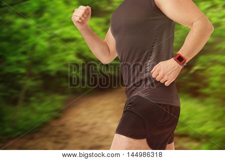 Man running with pulsometer on blurred forest background