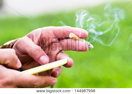 a young man smoking a cigarette. Smartphone on hands