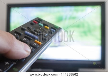 watching television, zapping  at home. Remote control