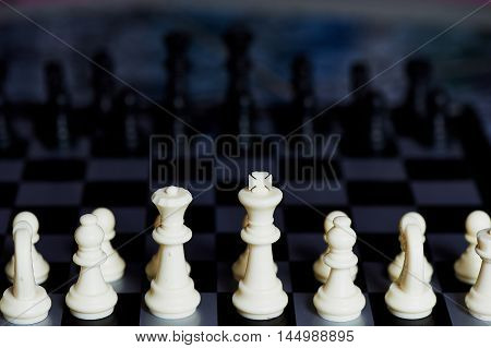 Chess pieces standing on black white chess . Macro
