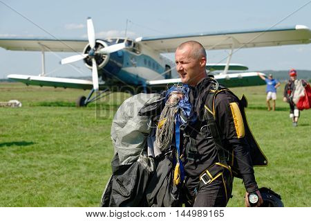 Kharkiv Ukraine - August 20 2016: Skydiver carries a parachute on background of Antonov An-2 aircraft after landing at the airfield Korotych Kharkov region Ukraine on August 20 2016