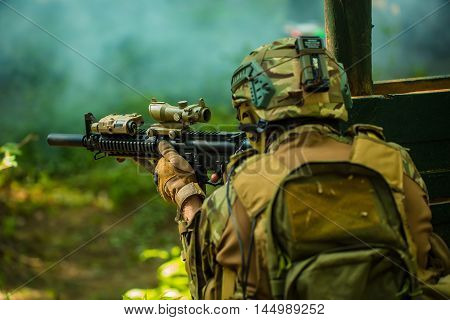 Soldier in military camouflage helmet sitting with backpack on back holding rifle aiming target in forest outdoor