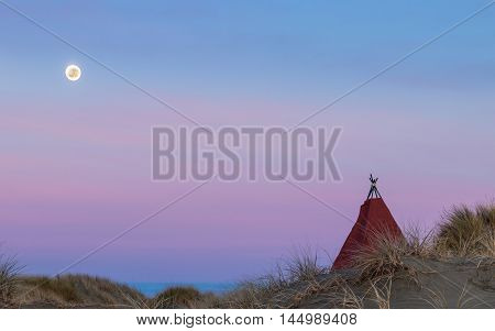Tepee on a beach sand dune with a bright moon in the dawn sky.