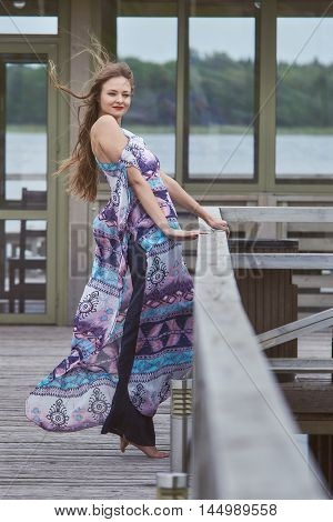 A young tall girl in elegant clothes, resting in a cafe. She drinks cocktails and dances on a wooden pier .Her dress fluttering in the wind. She laughs and smiles.A girl wearing a pale blue dress made of organic linen fabric.The design of the dress design