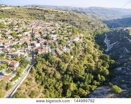 Aerial view of the picturesque village Arsos in Limassol Cyprus near the valley of river diarizos. View of the traditional stone and roof tiled houses and the lush forest of the mountain Laona.