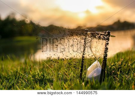Time is passing (Hourglass on grass field )