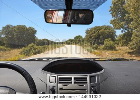 Car interior and gravel road on a sunny day. Summer holidays