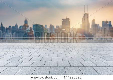 empty brick floor with city skyline background