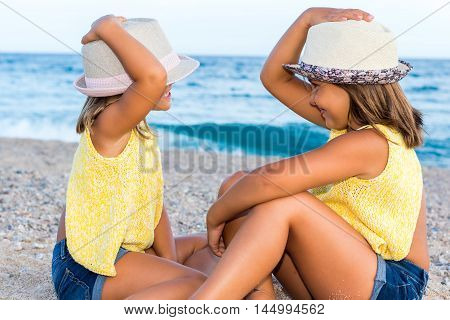 Close up portrait of little girls wearing hats sitting on beach.Side view of kids looking at each other.