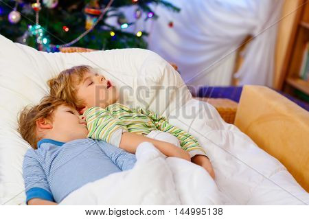Two little blond sibling boys sleeping in bed near Christmas tree with lights and illumination. Tired kids dreaming and relaxing. Happy family of two brothers.