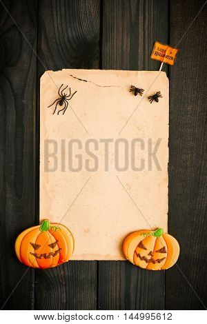Blank old paper sheet and gingerbread cookie over dark wooden background. Halloween invitation.