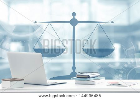 Law concept. Lawyer workplace with laptop and scales of justice design on blurred background.