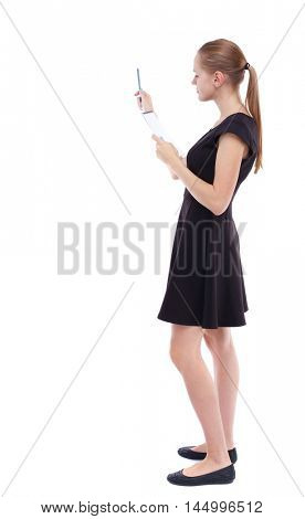back view of stands woman takes notes in a notebook. girl watching. Isolated over white background. Blonde in a short black dress check the records in a notebook.